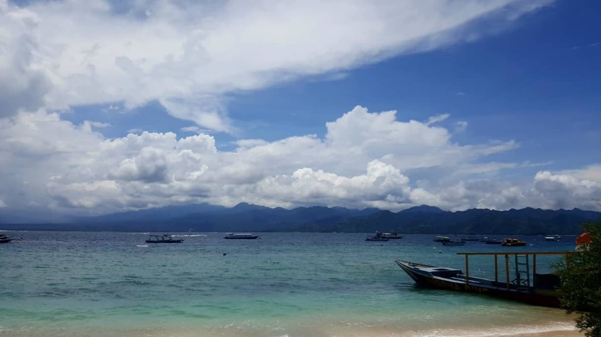 Girls Who Travel | A beach with crystal blue waters and a few calm boats off the coast of Bali