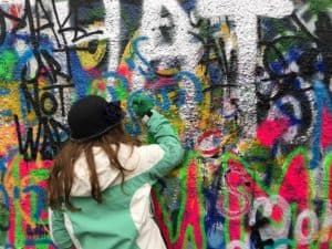 Girls Who Travel | Author Bethany paints on a graffiti wall