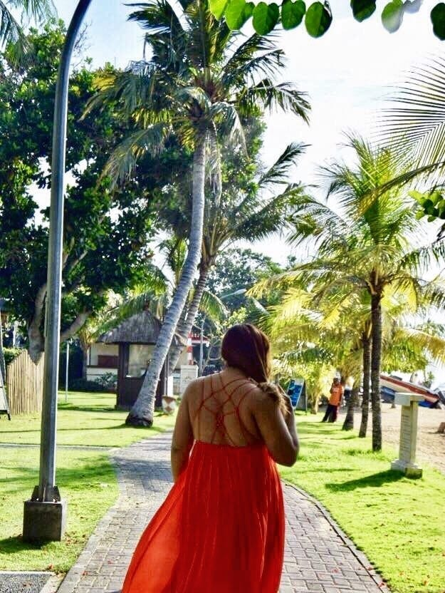 Girls Who Travel | Author Rachel wears a flowy red dress on a street lined with palm trees in Bali