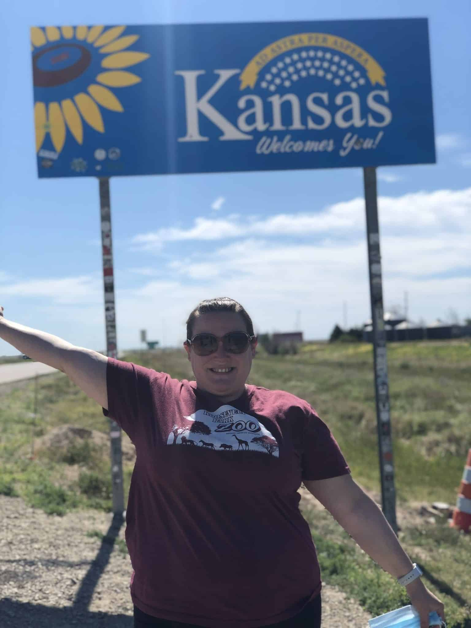 "Girls Who Travel | Author Jessica poses with the ""Welcome to Kansas"" sign on the Interstate"