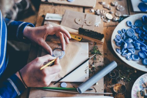Girls Who Travel - A woman carving shapes out of fimo clay, making jewelry on a messyworkbench.