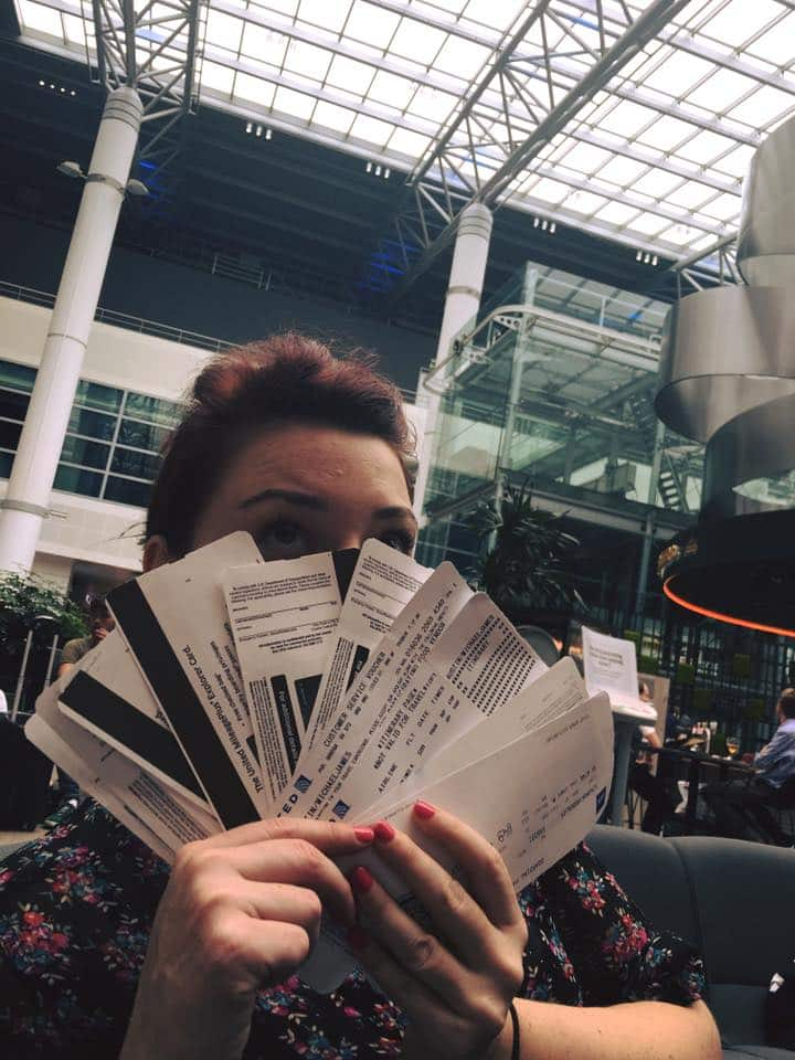 Arden fans herself with a stack of plane and train tickets