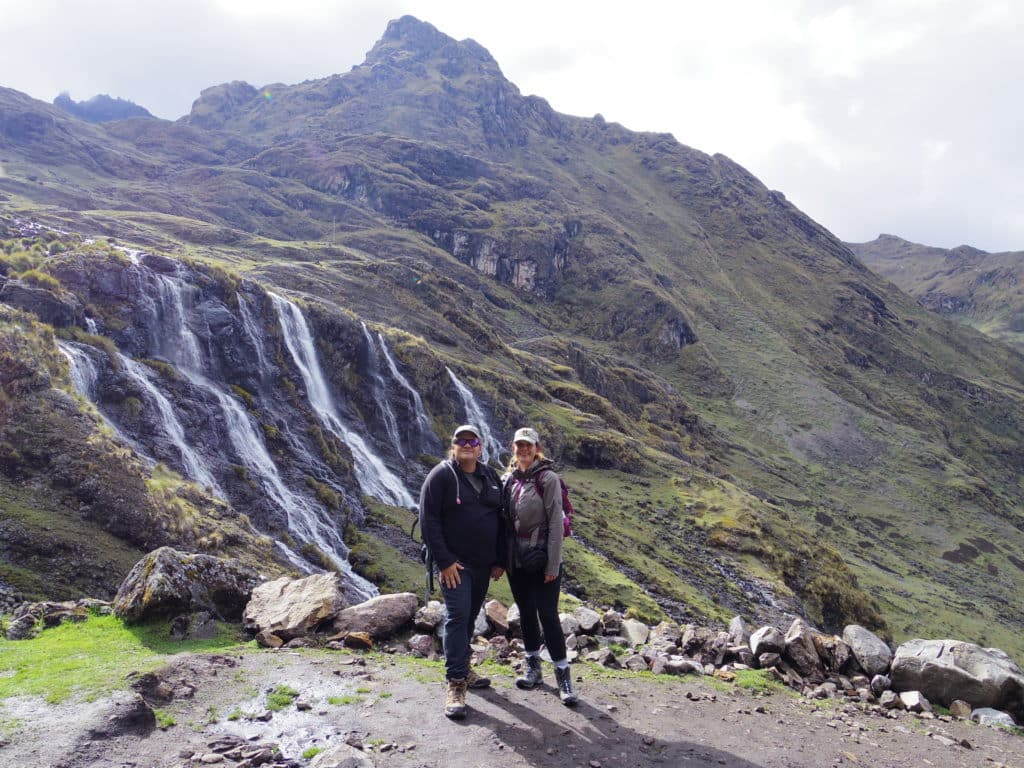 Jenny poses with her husband, TJ, in front of a mountain in Peru. Several small waterfalls flow down the luch, green mountain in the background.