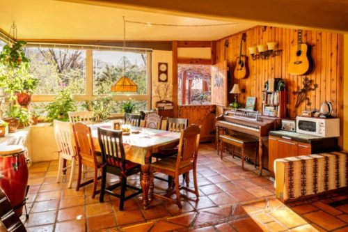 a very wooden dining room with many green plants and a cozy atmosphere