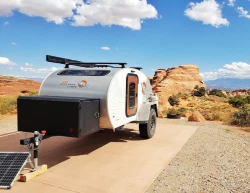 A silver teardrop shaped trailer with a black raven print parked in beautiful rocky landscape