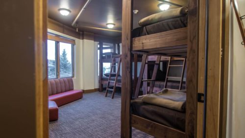 Her Adventures | a hostel dorm room with cabin style wooden bunk beds and a view of trees