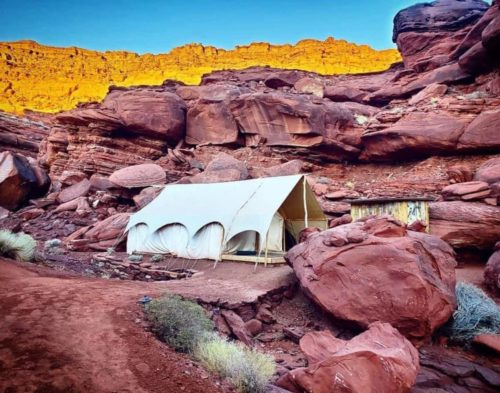 A white luxury tent hitched in the middle of red rocks